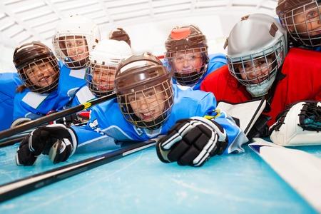 Fröhliche Jungs in Hockeyuniform, die auf der Eisbahn liegen