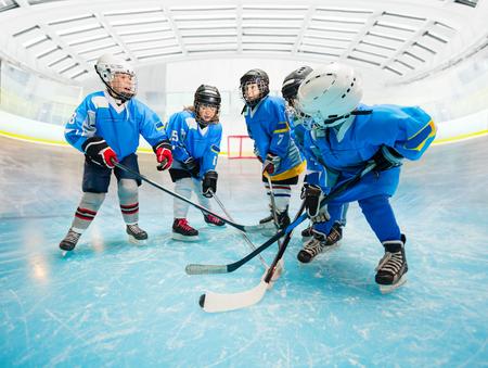 Childrens ice hockey team practicing on rink