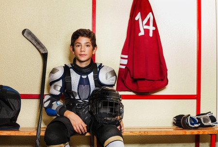 Boy sitting on the bench in ice hockey locker room Stok Fotoğraf