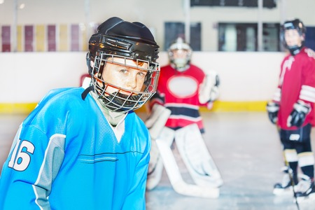 Junior hockey player in safety helmet and uniform