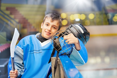 Young hockey player standing next to rink boards 免版税图像