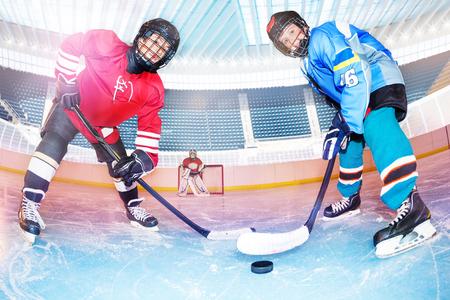 Les joueurs de hockey défient la rondelle sur la patinoire
