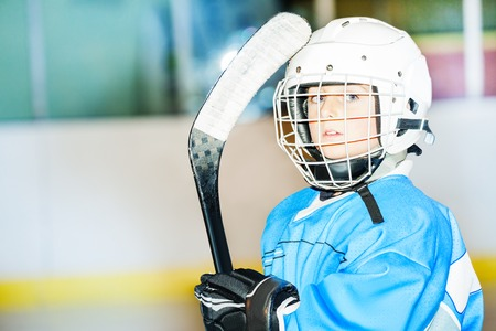 Little hockey player in helmet and blue uniform Stock Photo