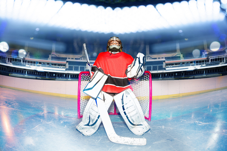 Boy goaltender under the lights of hockey stadium Stockfoto