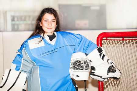 Happy girl goaltender posing after hockey match Banco de Imagens