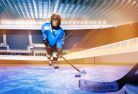 Boy learning to pass the puck at ice hockey rink Stockfoto