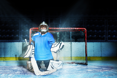 Young goaltender guards his net during hockey game Zdjęcie Seryjne