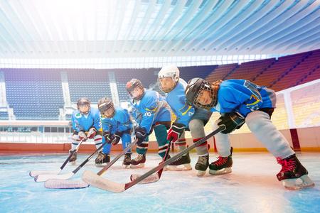 Drużyna hokejowa dla dzieci ustawia się na lodowisku