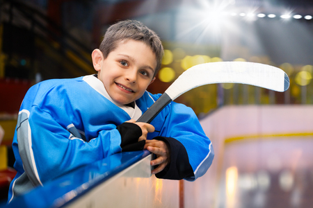 Boy with hockey stick leans on the boards of rink