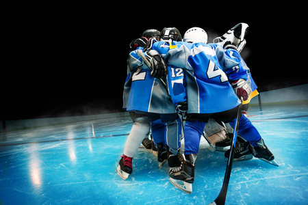 Hockey team standing in circle on ice rink Stock Photo