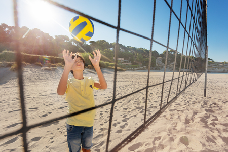 View through the net of boy playing volleyball