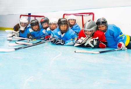 Joyful boys and girls laying on ice hockey rink