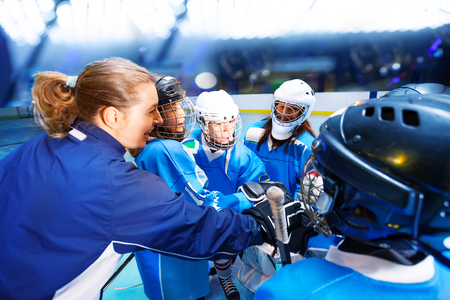 Coach and hockey players putting hands in huddle Imagens