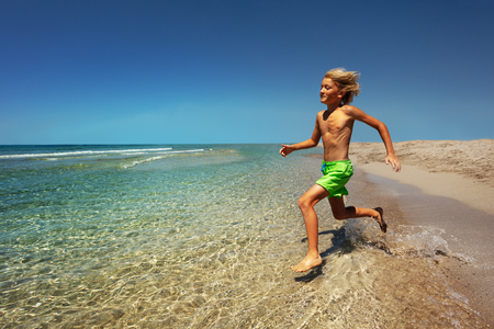 Young boy preparing to jump into the sea Imagens
