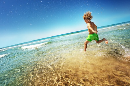 Boy running into the sea splashing and having fun