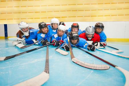 Happy hockey team laying on ice rink at stadium 版權商用圖片