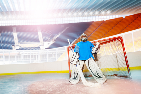 Young goalie guarding his net during hockey game