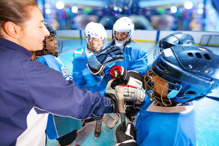 Coach and hockey team putting hands in huddle 版權商用圖片