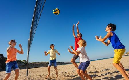 Jungen im Teenageralter, die Volleyball am Strand spielen