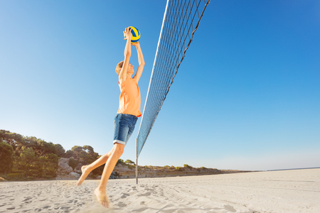 Junge, der den Ball beim Beachvolleyballspiel serviert