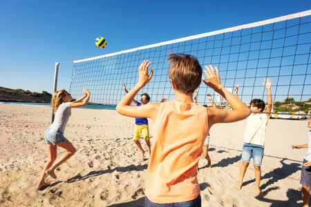 Sporty young girl passing volleyball over the net