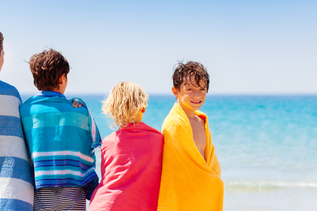 Happy boy drying off on the beach with his friends Stock Photo