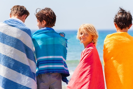 Boy in beach towel after sea swimming with friends