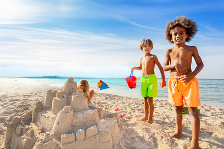 Kids having fun, building sandcastle on the beach