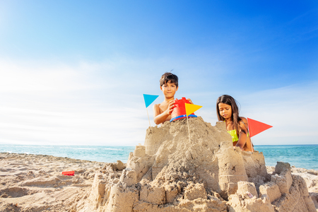 Boy and girl building sand castle at the seaside