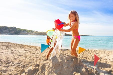 Entzückendes Mädchen, das Strandspiele mit Freunden spielt