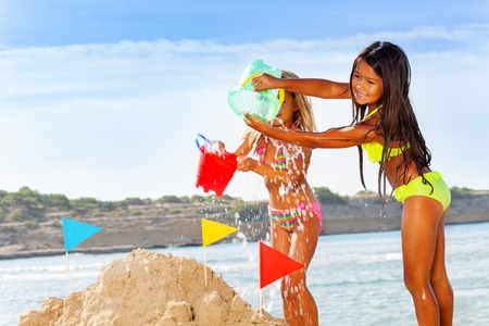 Happy girls friends making sandcastle on the beach Banque d'images