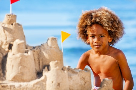 Boy building sandcastle on the beach in summer