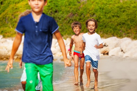 Active boys running one after another on the beach Stok Fotoğraf