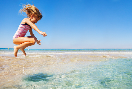 Little girl having fun jumping at shallow water