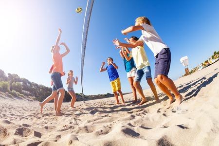 Boy serving the ball during beach volleyball match Reklamní fotografie