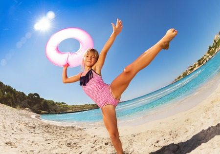 Happy girl dancing with rubber ring on sandy beach