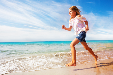 Beautiful girl running along sandy beach in summer