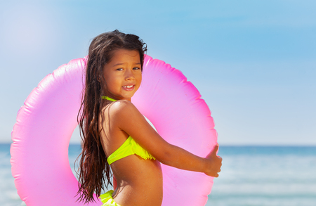 Little Asian girl with swimming ring on the beach
