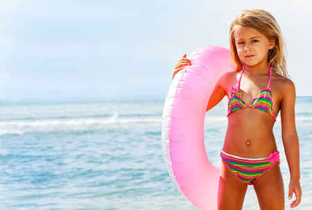 Beautiful girl posing with swim ring on the beach Banco de Imagens