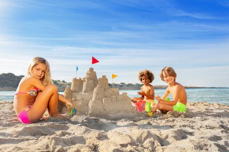 Three happy friends building sandcastle on beach