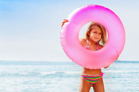 Cute little girl looking through big swimming tube