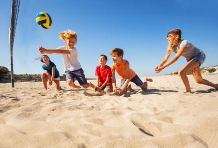 Niño haciendo pasar bump durante el juego de voleibol de playa Foto de archivo