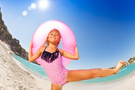 Happy girl dancing with rubber ring on the beach Stockfoto