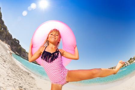 Ragazza felice che balla con l'anello di gomma sulla spiaggia