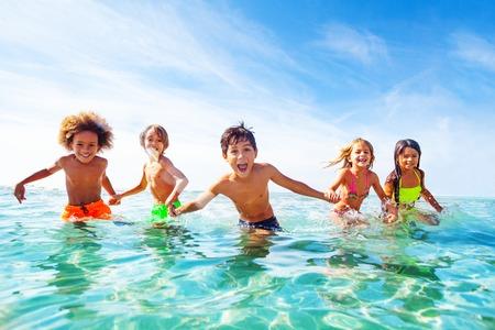 Enfants riant et jouant dans l'eau au bord de la mer