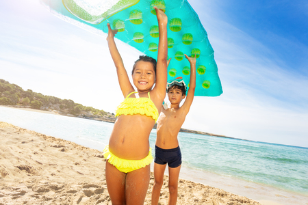 Cute kids with air mattress overhead on the beach