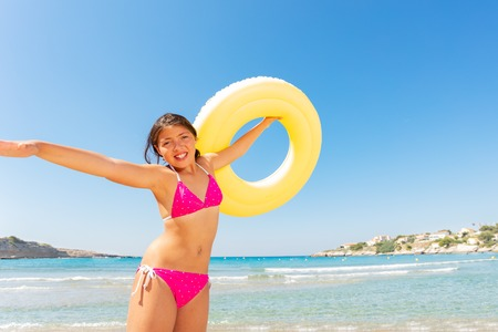 Funny girl with yellow rubber ring on the beach Stockfoto