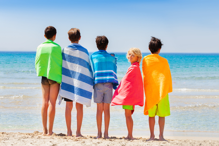 Boys dry off with beach towel after sea swimming