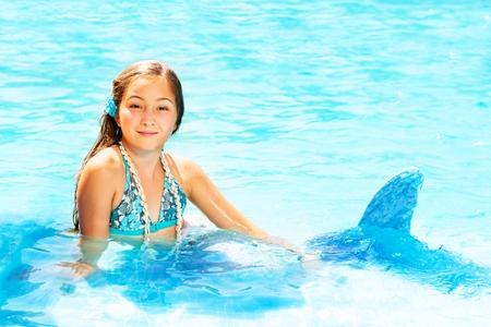 Beautiful mermaid in blue water of swimming pool