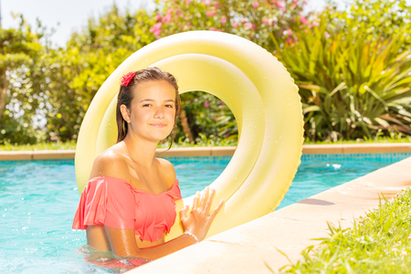 Beautiful girl with swim ring in swimming pool 스톡 콘텐츠 - 114504783